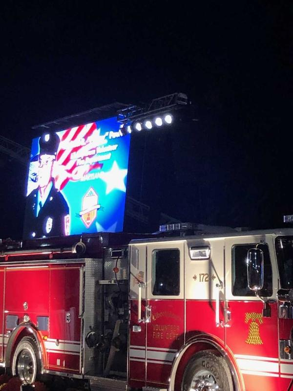 During the candlelight vigil Saturday night, a photo of Michael Powers was shown on a screen above the Libertytown engine he drove on his final alarm. (Photo by Chip Jewell)