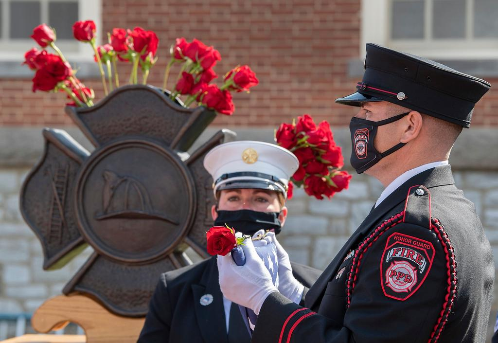 An honor guard member waits to deliver a flag, rose and badge. (NFFF photo)