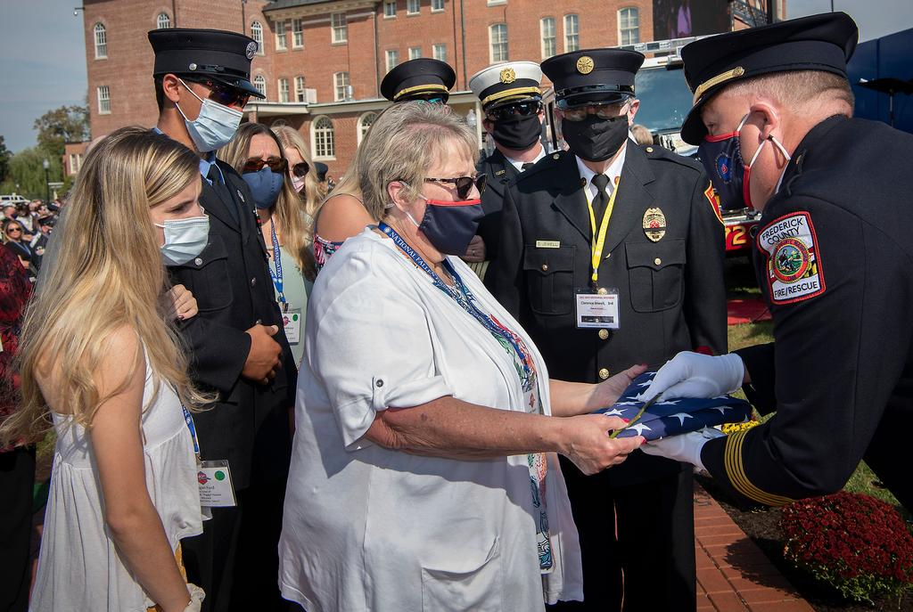 Linda Powers receives a flag, a rose and a badge from Chief Tom Coe during the service. (NFFF photo)