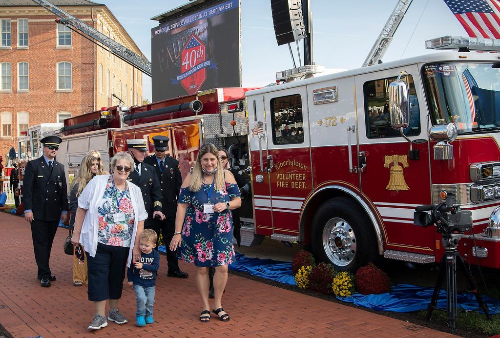 Members of the Powers family walk by the engine that their loved one drove on his final call. (NFFF photo)
